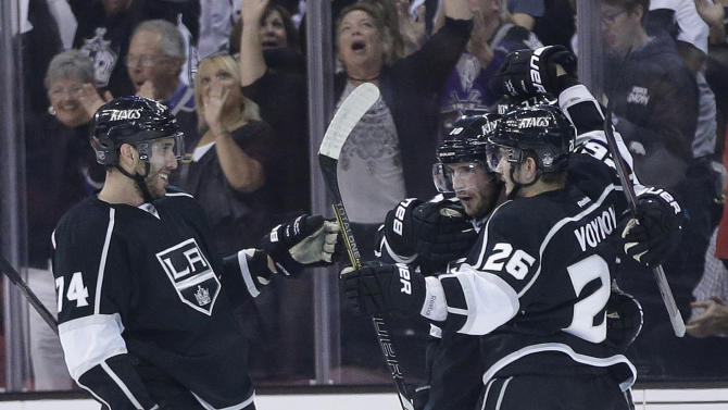 Los Angeles Kings' Slava Voynov (26) celebrates his first-period goal against the San Jose Sharks with teammates Dwight King, left, and Jeff Carter in Game 1 of a second-round NHL hockey Stanley Cup playoff series, in Los Angeles, Tuesday, May 14, 2013. (AP Photo/Chris Carlson)