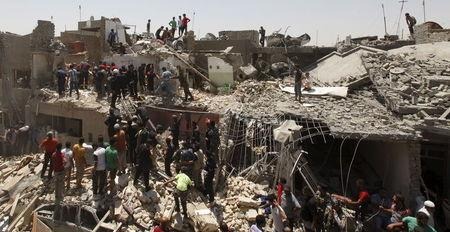 People stand outside damaged houses after an Iraqi plane accidentally dropped a bomb in Ni'iriya district in Baghdad