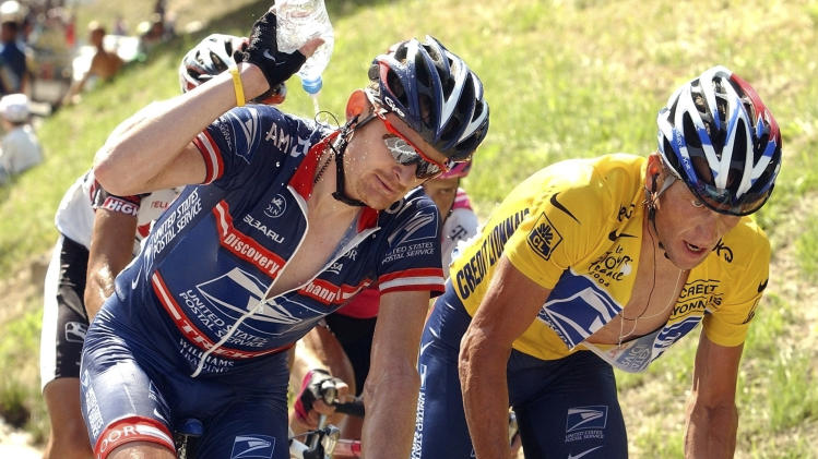 FILE - In this July 22, 2004, file photo, Lance Armstrong, right, climbs the ascent of the La Croix Fry pass as teammate Floyd Landis, left, pours water over his neck during the 17th stage of the Tour de France cycling race between Bourg-d'Oisans and Le Grand Bornand, French Alps. Landis, who was stripped of the 2006 Tour de France title for doping, has filed a federal whistle-blower lawsuit that accused Armstrong of defrauding the U.S. Postal Service amidst doping accusations. The Justice Department has yet to decide whether it will join the suit as a plaintiff. (AP Photo/Bernard Papon, Pool, File)
