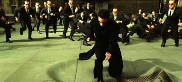 Hordes of copies of Agent Smith ( Hugo Weaving ) swarm Neo ( Keanu Reeves ) in Warner Brothers' The Matrix: Reloaded