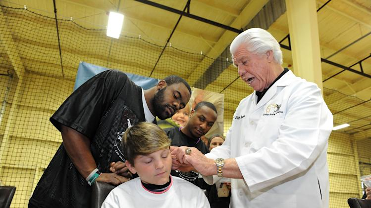 New Orleans Saints Mark Ingram and Darren Spoles look on as  Bill Austin, founder of Starkey Hearing Foundation, fits a young boy with a hearing aid at The Citi Garth Brooks Super Pro Camp on Friday, Feb. 1, 2013 in New Orleans. (Photo by Cheryl Gerber/Invision for Starkey Hearing Foundation/AP Images)