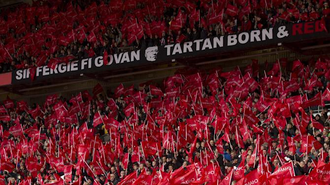 Supporter wave red flags before Manchester United manager Alex Ferguson's last home game in charge of the club ahead of their English Premier League soccer match against Swansea, at Old Trafford Stadium, Manchester, England, Sunday May 12, 2013. (AP Photo/Jon Super)