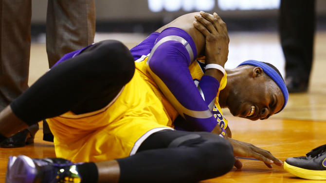 L.A. Lakers Dwight Howard falls to the court and grabs his right shoulder in pain in the 4th quarter of the game against the Phoenix Suns Wednesday Jan. 30, 2013.  The Lakers, who had won three straight _ all at home, lost Dwight Howard when he reinjured his right shoulder with 6:57 to play. (AP Photo/The Arizona Republic, Rob Schumacher)