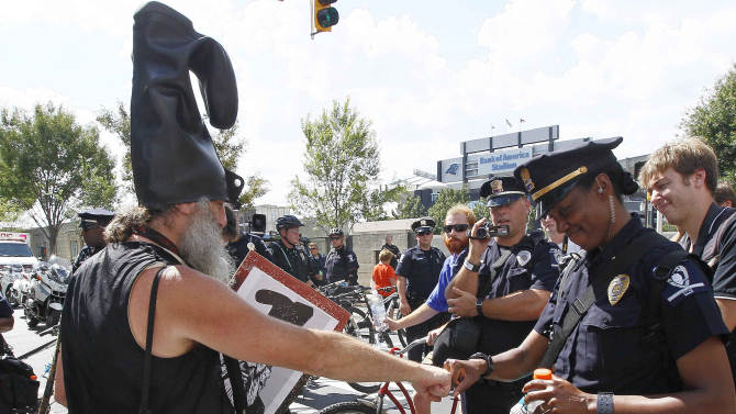 Police Capt. E.D. Patterson fist bumps with demonstrator Vermin Supreme during a protest march, Sunday, Sept. 2, 2012, in Charlotte, N.C. Demonstrators are protesting before the start of the Democratic National Convention. (AP Photo/Gerry Broome)