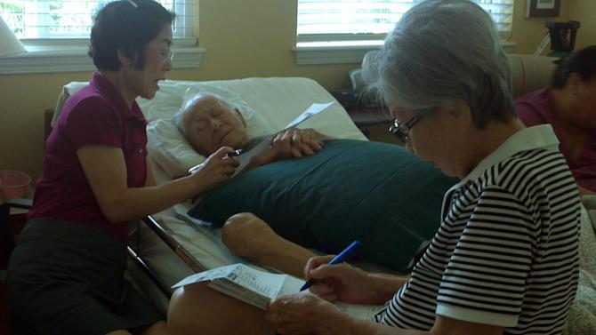 In this Oct. 17, 2012 photo provided by Irene Tanabe, Frank Tanabe, center, gets help from his daughter Barbara Tanabe, left, to fill out his absentee ballot in Honolulu while his wife Setsuko Tanabe sits in the foreground. The photo of the 93-year-old World War II veteran casting what will likely be his last ballot has captured the hearts of tens of thousands of Internet users. (AP Photo/Irene Tanabe)