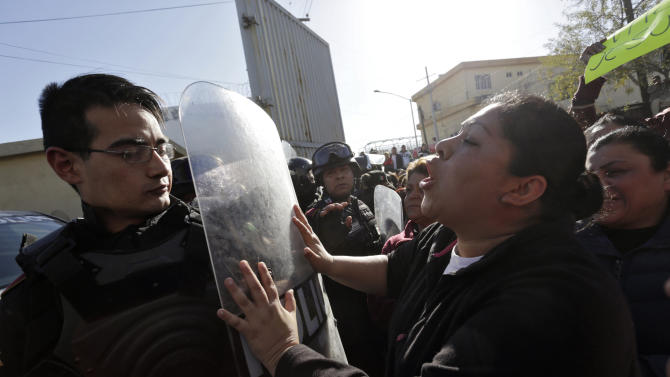 A family member of an inmate pushes the shield of a police officer outside the Topo Chico prison in Monterrey