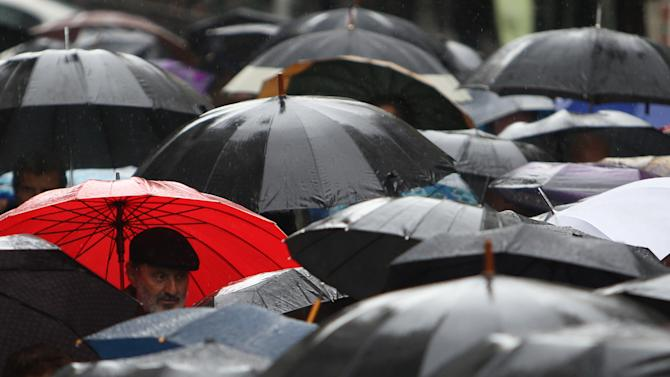 Pensioners gather under umbrellas in heavy rain during a protest outside the Labor Ministry in central Athens, Thursday, Feb. 14, 2013. Several hundred pensioners marched to protest the new tax increases. The poverty line in Greece is currently set at a personal income of less than euro 7,200 ($9,700) per year. (AP Photo/Thanassis Stavrakis)