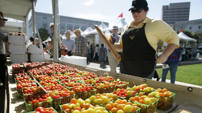 File - In this Aug. 29, 2008, file photo, Benina Burroughs of Merced, Calif., looks over a display of cherry tomatoes by Farmers with ALBA from Salinas, Calif., at a farmer's market during Slow Food Nation in San Francisco. Pushed by the rising popularity of eating locally and healthily, the number of farmers markets climbed by 9.6 per cent nationally over the past year, according to the USDA. There now are more than 7,800 markets in the U.S. after 18 years of steady increases, according to a report to be announced Friday. (AP Photo/Eric Risberg, File)
