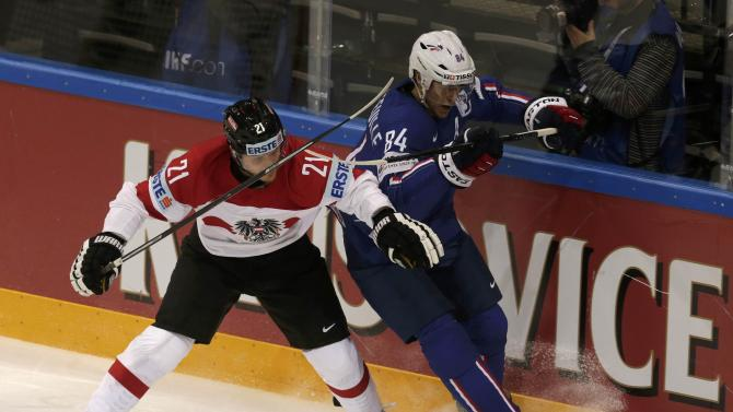 Austria's Geier fights for the puck with France's Hecquefeuille during their Ice Hockey World Championship game at the O2 arena in Prague