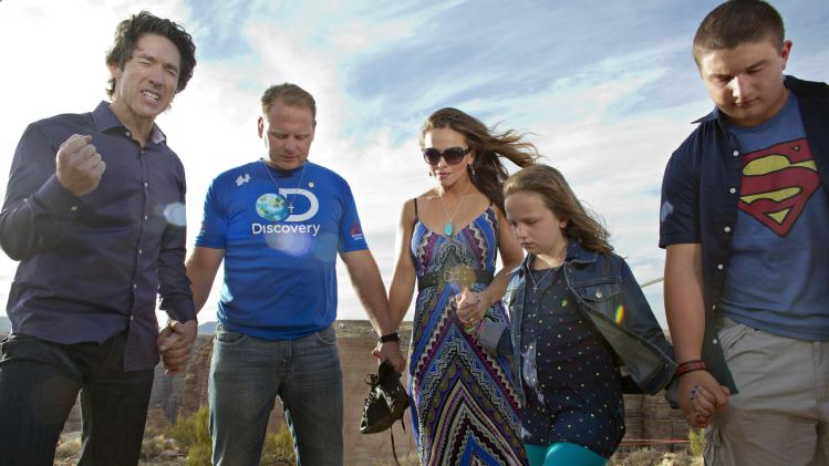 Preacher Joel Osteen, left, leads a prayer with Nik Wallenda, second from left, his wife Erendira, daughter Evita and son Yanni before Wallenda walked a 2-inch-thick steel cable that took him a quarter mile over the Little Colorado River Gorge in northeastern Arizona on Sunday, June 23, 2013. The daredevil successfully traversed the tightrope strung 1,500 feet above the chasm near the Grand Canyon in just more than 22 minutes, pausing and crouching twice as winds whipped around him and the cable swayed. (AP Photos/Discovery Channel, Tiffany Brown)