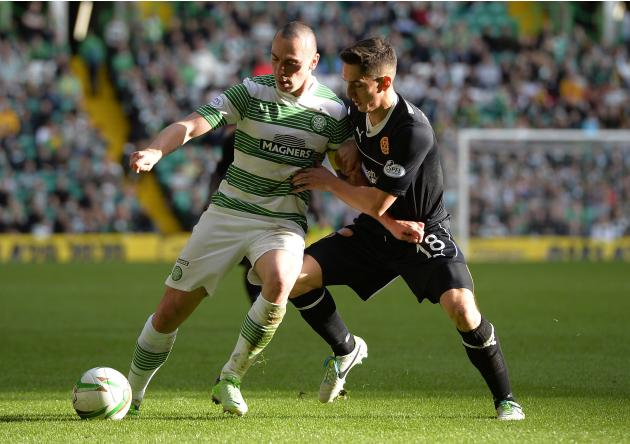 Motherwell's Stuart Carswell challenges Celtic's Scott Brown during their Scottish Premier League soccer match at Celtic Park