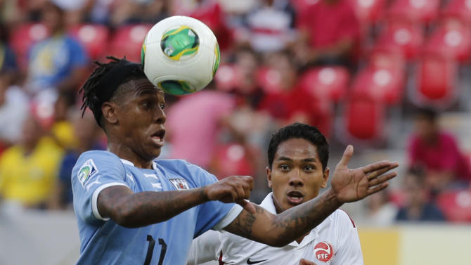 Tahiti's Jonathan Tehau, back, looks at Uruguay's Abel Hernandez heading the ball during a soccer Confederations Cup group B match at the Arena Pernambuco in Recife, Brazil, Sunday, June 23, 2013. (AP Photo/Eugene Hoshiko)