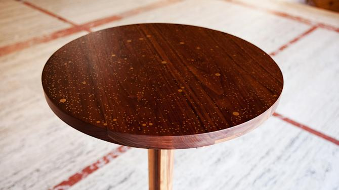 This undated photo provided by Asher Israelow Studio shows a detail of the top of a Star Map walnut table from the Serenade series, a group of tables built for the New York City Ballet that map the history of dance through the stars.  Brooklyn furniture designer Asher Israelow (www.asherisraelow) will create a custom Star Map table by researching what the night sky looked like for your specific date, and reproducing it with brass inlay on walnut. (AP Photo/Asher Israelow Studio, Jamie Goldenberg)