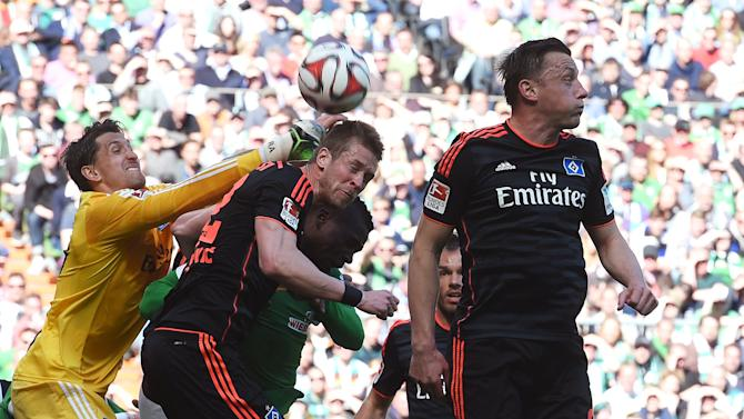 Hamburg SV's goalie Adler and his team mates Rajkovic and  Olic save the ball during their German Bundesliga first division soccer match against Werder Bremen in Bremen