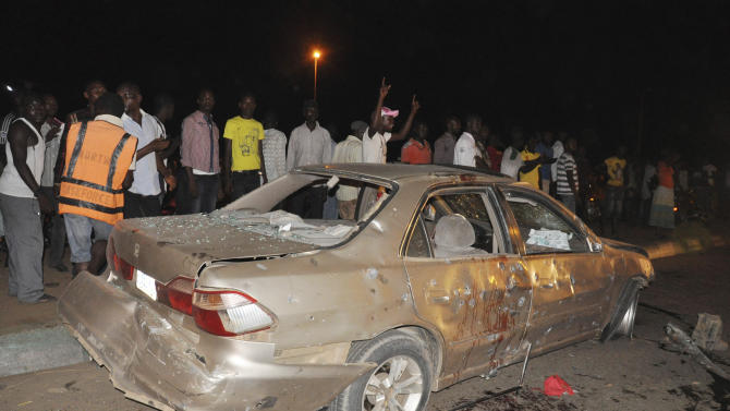 People gather near the damaged car following a bomb explosion in Abuja, Nigeria, Thursday, May 1, 2014. A car bomb exploded on a busy road in Nigeria's capital late Thursday, killing at least 12 people days before the city is to host a major international economic forum. (AP Photo/Gbemiga Olamikan)