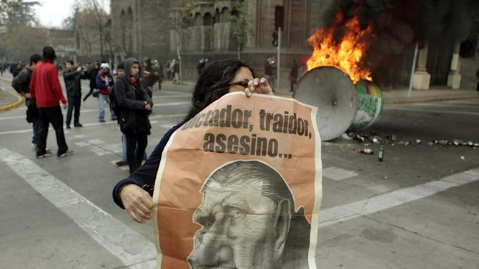 "A woman holds a poster depicting Gen. Augusto Pinochet during a protest against the premiere of a documentary about Pinochet in Santiago, Chile, Sunday June 10, 2012.  Police used tear gas and water cannons to try to disperse hundreds of anti-Pinochet demonstrators against the documentary about the run-up to his dictatorship years and casting him as a national hero who saved Chile from communism, The writing reads in Spanish ""Dictator, traitor, killer and always thief"".(AP Photo/Luis Hidalgo)"