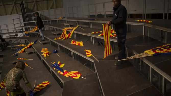 """In this photo taken on Thursday, Nov. 8, 2012, supporters of center-right Catalan Nationalist Coalition (CiU) leader Artur Mas collect pro-independence """"estelada"""" flags and """"senyeras"""" Catalan flags left behind by supporters after a campaign meeting in Barcelona, Spain. Catalonia holds elections on Sunday that will be seen as a test of the regional government's plans to hold a referendum on independence, and one of the key issues emerging is the theoretical place of a free Catalonia in Europe. (AP Photo/Emilio Morenatti)"""