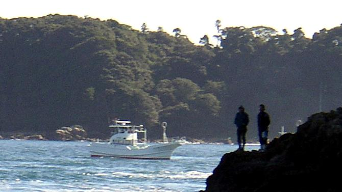File photo taken in November 2003 shows two dolphins being herded by fishing boats into a cove near the village of Taiji, central Japan