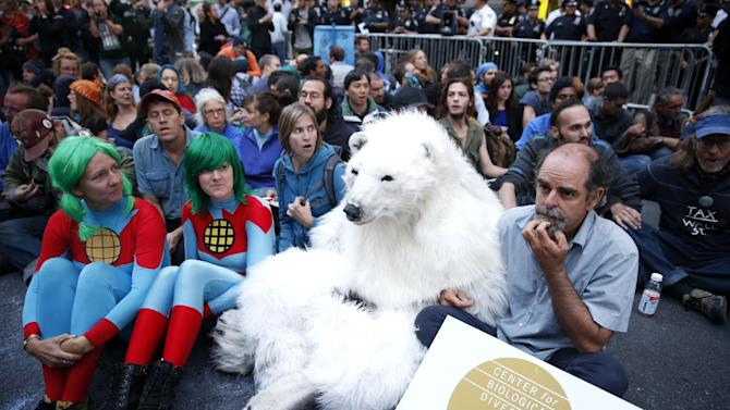 Protesters, including one dressed as a polar bear, sit at the intersection of Wall St. and Broad St. in New York, Monday, Sept. 22, 2014. The protesters were trying to draw attention to the connection between capitalism and environmental destruction. Eventually at least fifty protesters that would not move from the intersection were taken into custody. (AP Photo/Seth Wenig)