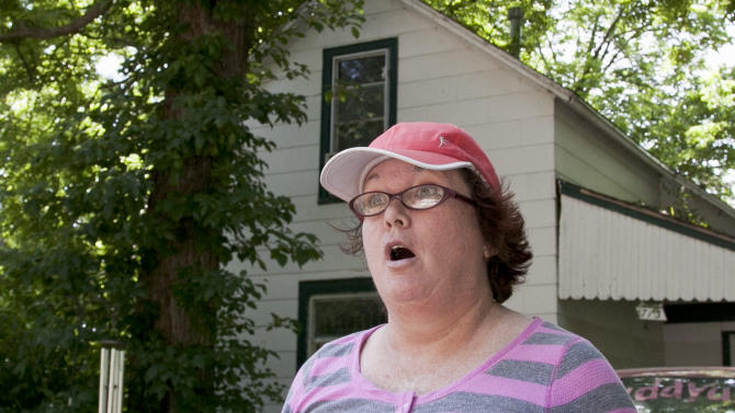 Naomi Raposo, who lives across the street from the Schilling house in Plattsmouth, Neb., reacts Tuesday, May 22, 2012, to news that autopsy results have confirmed the bodies of two people found in Lake Manawa State Park south of Council Bluffs, Iowa on Sunday, May 20, are those of missing Nebraska woman Charlotte Schilling, 41, and her 10-year-old son, Owen.The mother and son went missing from their Plattsmouth, Neb., home on May 10. (AP Photo/Nati Harnik)