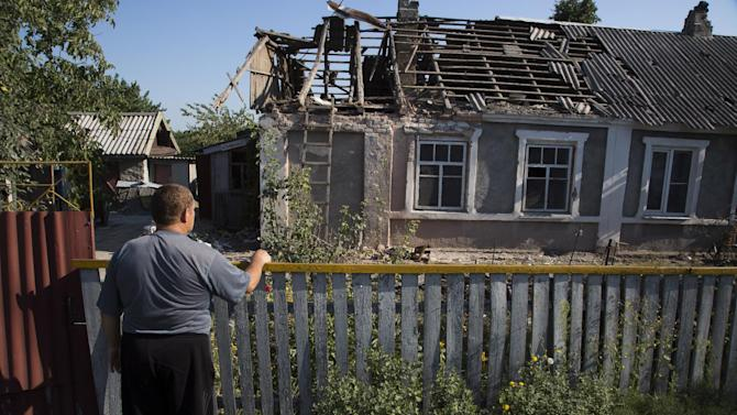 A local resident calls to his neighbor from a damaged house after shelling in Petrovsky district in the city of Donetsk, eastern Ukraine Tuesday, Aug. 5, 2014. Ukrainian troops took control of a checkpoint Tuesday on the western edge of the pro-Russian rebel-held city of Donetsk as the government makes further gradual advances to quash separatist forces in the east. (AP Photo/Dmitry Lovetsky)