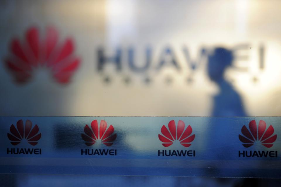 In this Monday, Oct. 8, 2012 photo, a man walks near company logos at a R&D center of Huawei Technologies Inc. in Wuhan, in central China's Hubei province. Eager to expand in the United States, China's biggest technology companies face American anxiety about security and rising Chinese competition. (AP Photo)  CHINA OUT