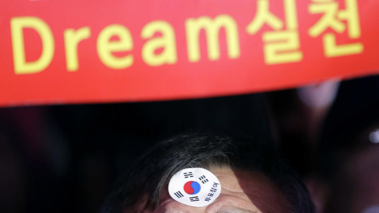 "A supporter of South Korean presidential candidate Park Geun-hye of the ruling Saenuri Party cheers up during her campaign rally in Seoul, South Korea, Tuesday, Dec. 18, 2012. South Korea's presidential election is scheduled for Dec. 19. The sign reads "" Fulfill Dream."" (AP Photo/Lee Jin-man)"