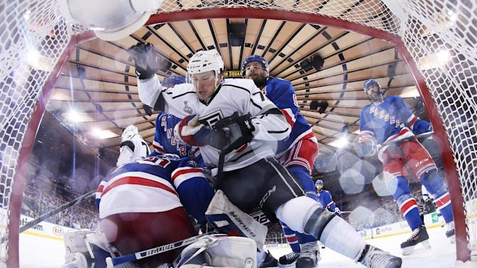 New York Rangers defenseman Dan Girardi (5) grabs Los Angeles Kings center Tyler Toffoli (73) as he falls toward the net in the third period during Game 4 of the NHL hockey Stanley Cup Final, Wednesday, June 11, 2014, in New York. The Rangers won 2-1