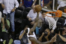 Miami Heat small forward LeBron James (6) scores the winning basket as Indiana Pacers forwards Paul George (24) Sam Young (4) defend during overtime in Game 1 in their NBA basketball Eastern Conference finals playoff series, Thursday, May 23, 2013 in Miami. The Heat won 103-102. (AP Photo/Wilfredo Lee)
