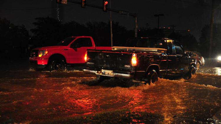 Residents try to pass through a flooded intersection in Downtown Oklahoma City after multiple tornado's passed through Central Okla. on Friday May 31, 2013 in Oklahoma City. (AP Photo/Nick Oxford)