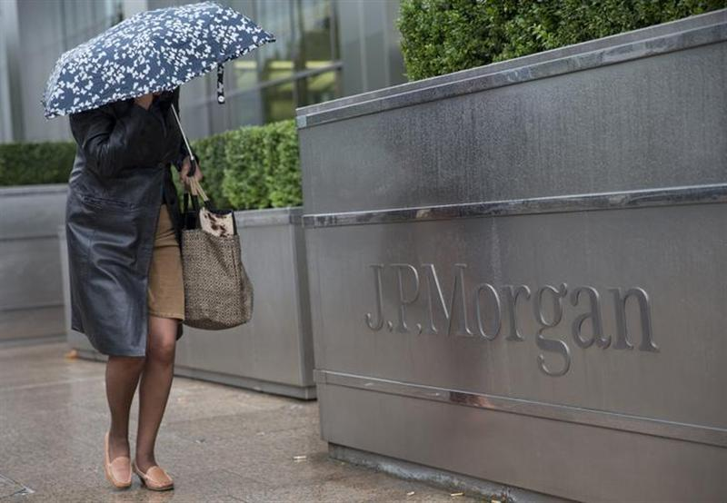 A pedestrian walks past the Canary Wharf offices of JP Morgan in London September 19, 2013.