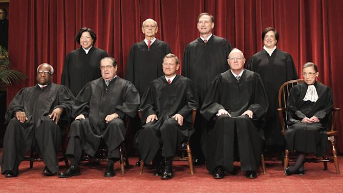 FILE -In this Oct. 8, 2010 file photo, members of the Supreme Court gather for a group portrait at the Supreme Court in Washington. Seated from left are: Associate Justices Clarence Thomas, Antonin Scalia, Chief Justice John Roberts, Associate Justices Anthony M. Kennedy, and Ruth Bader Ginsburg. Standing, from left are: Associate Justices Sonia Sotomayor, Stephen Breyer, Samuel Alito Jr., and Elena Kagan. A historic Supreme Court term ended with a flourish of major rulings that marked a bitter defeat for racial minorities and a groundbreaking victory for gay rights, all in the space of a day. The justices struck down parts of two federal laws _ the Voting Rights Act and the Defense of Marriage Act _ that were passed with huge bipartisan majorities of Congress. Yet, only one justice at the center of this conservative-leaning court, Anthony Kennedy, was on the winning side both times. Kennedy joined the four more conservative justices on voting rights and he was with his liberal colleagues in the gay marriage case. (AP Photo/Pablo Martinez Monsivais, File)
