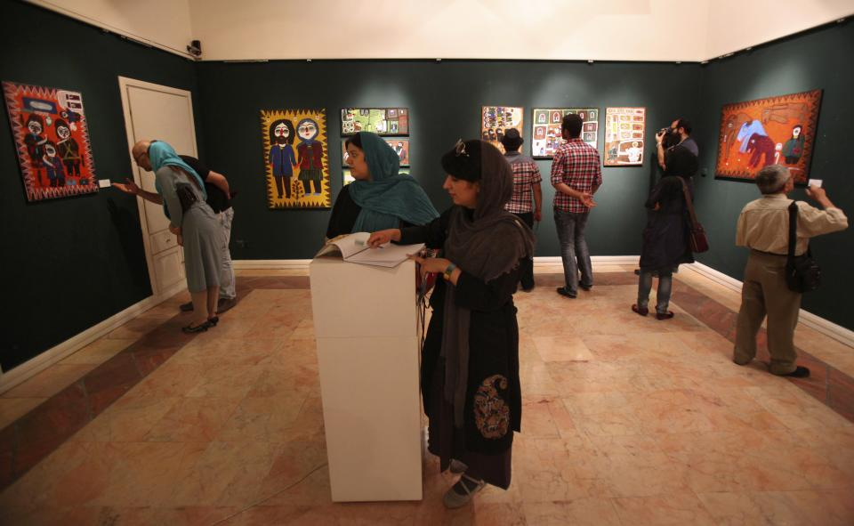 In this picture taken on Monday, July 1, 2013, Iranians visit an art gallery with paintings, in Tehran, Iran. (AP Photo/Vahid Salemi)