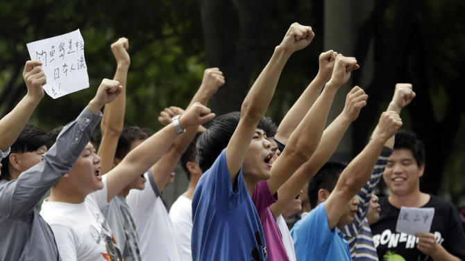 """A Chinese man holds up a piece of paper with the words """" Diaoyu island belongs to China, Japanese get out"""" as he protests with others outside the Japanese embassy in Beijing, China Tuesday, Sept. 11, 2012. Chinese government ships are patrolling near contested East China Sea islands in a show of anger after Tokyo moved to assert its control in the area. Beijing warned Monday that Japan would suffer unspecified consequences if Tokyo purchased the islands from private owners, as it formally did Tuesday.(AP Photo/Ng Han Guan)"""