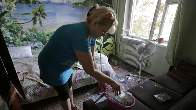 Marina Barsuk clears broken glass inside her apartment after overnight shelling in Donetsk, eastern Ukraine, Friday, Aug. 8, 2014. At least three civilians have been killed and another 10 wounded in overnight shelling of the main rebel stronghold in eastern Ukraine besieged by government forces, officials said. (AP Photo/Sergei Grits)