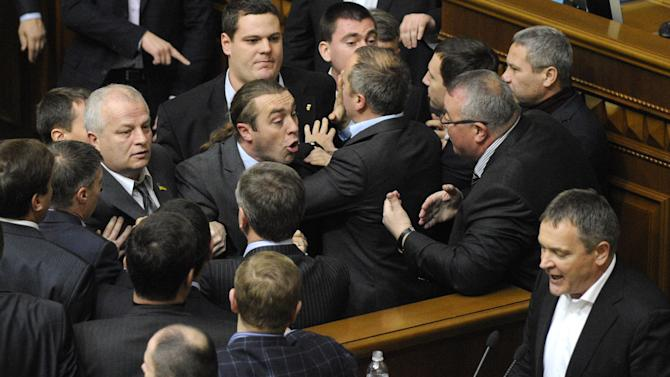 Ukrainian lawmakers fight around the rostrum during the first session of Ukraine's newly elected parliament in Kiev, Ukraine, Thursday, Dec. 13, 2012. A violent brawl between supporters of the president and opposition lawmaker broke out in parliament on Thursday, nearly overshadowing the naming of a new pro-government speaker to lead the fractious body. (AP Photo/Sergei Chuzavkov)