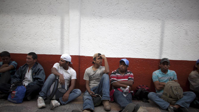 In this May 17, 2012 photo, migrants sit outside the mayor's residence after protesting violence against migrants in Lecheria, on the outskirts of Mexico City. While the number of Mexicans heading to the U.S. has dropped dramatically, a surge of Central American migrants is making the 1,000-mile northbound journey this year, fueled in large part by the rising violence brought by the spread of Mexican drug cartels. (AP Photo/Alexandre Meneghini)