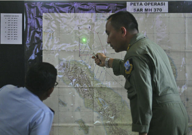 Indonesian Air Force officers examine a map of the Malacca Strait during a briefing following a search operation for the missing Malaysia Airlines Boeing 777, at Suwondo air base in Medan, North Sumat