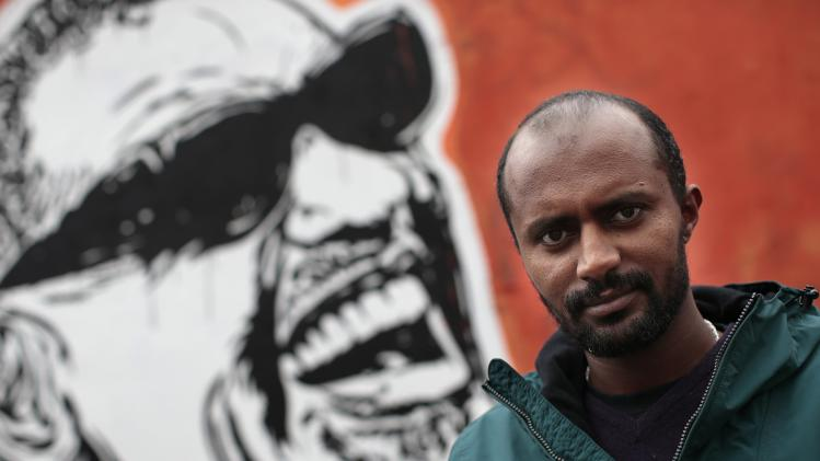 Director Dagmawi Yimer from Ethiopia poses next to a mural in downtown Rome