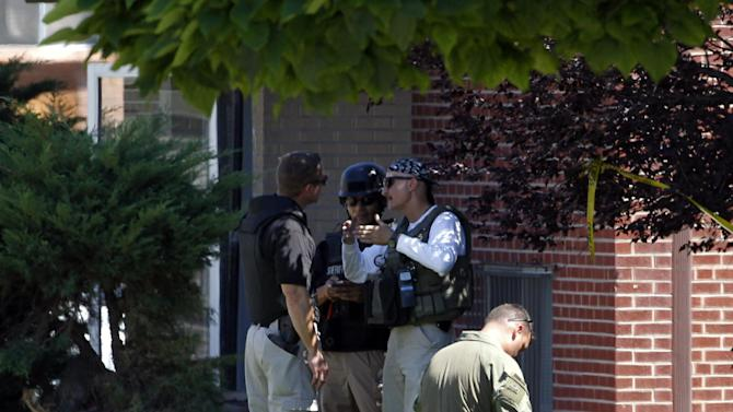 """Federal agents outside the apartment of James Holmes in Aurora, Colo., Saturday, July 21, 2012.  Federal authorities detonated one small explosive and disarmed another inside Holmes' apartment, but several other explosive devices remained, said Aurora police Sgt. Cassidee Carlson. Twelve people were killed and dozens were injured in a shooting attack early Friday at a packed movie theater during a showing of the Batman movie, """"The Dark Knight Rises.""""   Police have identified Holmes, 24, as the suspected shooter. (AP Photo/Ed Andrieski)"""