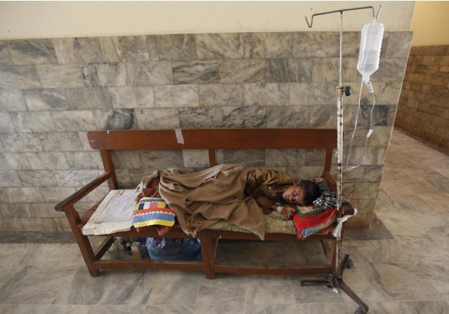 Nand Lal, a 10-year-old who was displaced from a drought-stricken area suffers from a chest infection, sleeps on a bench outside a ward in Civil Hospital Mithi in the Sindh province
