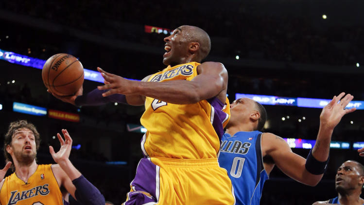Los Angeles Lakers' Kobe Bryant, center, shoots against Dallas Mavericks' Shawn Marion (0) as Elton Brand (42) and Lakers' Pau Gasol (16) watch in the first half of an NBA basketball game in Los Angeles, Tuesday, Oct. 30, 2012. (AP Photo/Jae C. Hong)