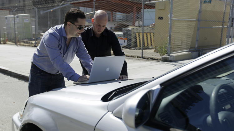 In this photo taken Tuesday, Aug. 16, 2011, security consultants Don Bailey, left, and Mathew Solnik, right, with iSEC Partners, demonstrate with a computer how they force cars with certain alarm systems to unlock their doors and start their engines by sending them text messages in San Francisco. (AP Photo/Eric Risberg)