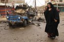An Iraqi woman passes by the scene of a car bomb attack in Kamaliyah neighborhood, a predominantly Shiite area of eastern Baghdad, Iraq, Monday, May 20, 2013. A wave of car bombings across Baghdad&#039;s Shiite neighborhoods and in the southern city of Basra killed and wounded dozens of people, police said. (AP Photo/ Hadi Mizban)
