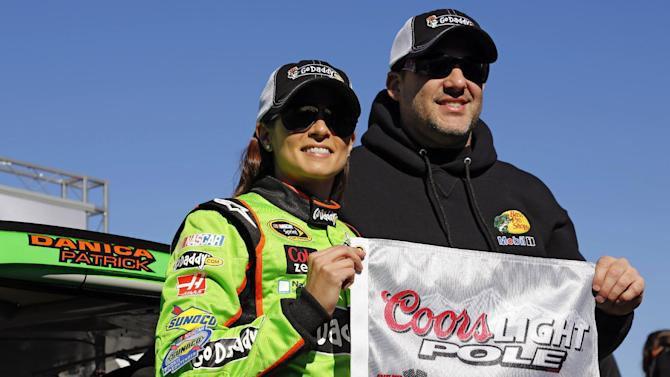 Danica Patrick, left, displays the flag with Tony Stewart after winning the pole during qualifying for the NASCAR Daytona 500 Sprint Cup Series auto race at Daytona International Speedway, Sunday, Feb. 17, 2013, in Daytona Beach, Fla. Patrick became the first woman to secure the top spot for any Sprint Cup race. (AP Photo/Terry Renna)