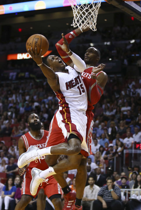 Houston Rockets' Dwight Howard (12) is unable to block Miami Heat's Mario Chalmers (15) during the first half of an NBA  basketball game in Miami, Sunday, March 16, 2014