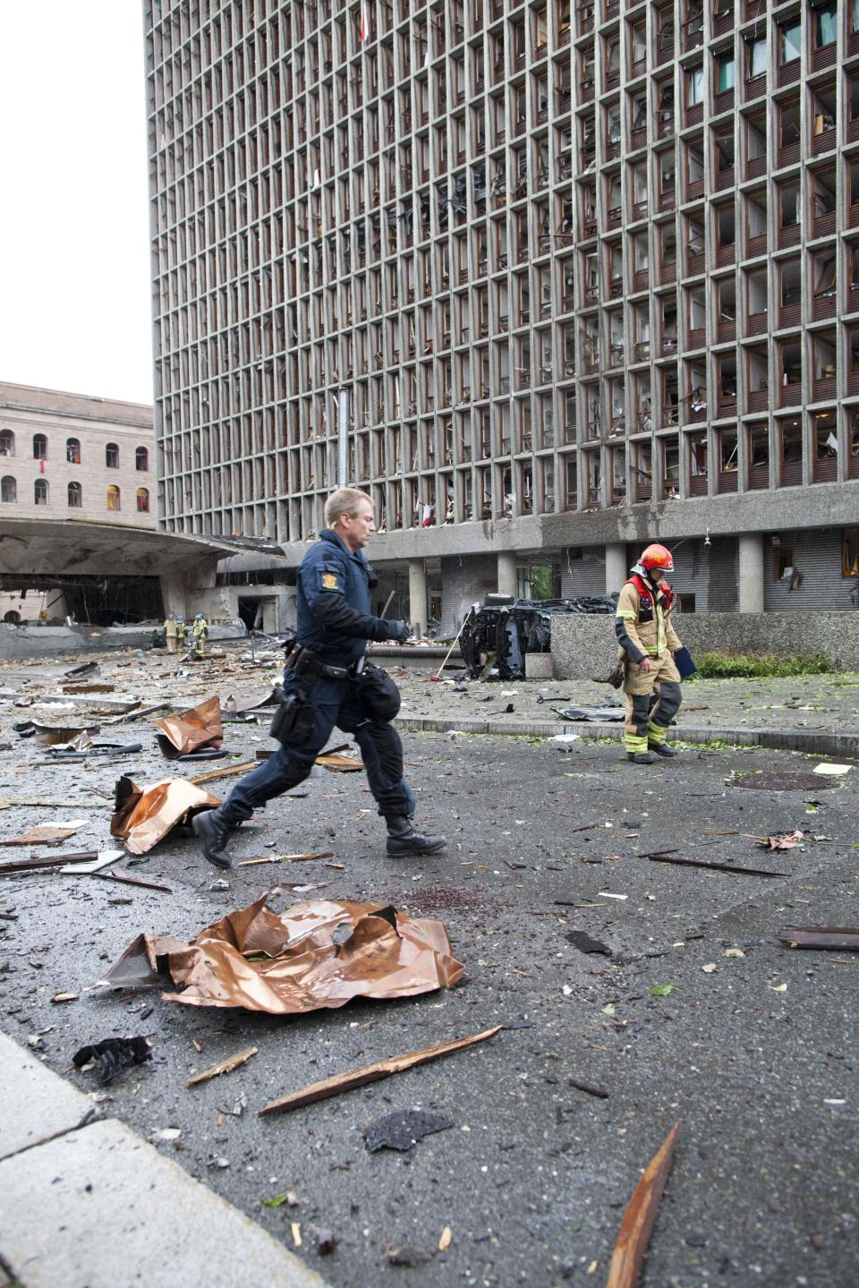 An officer responds in the center of Oslo, Friday July 22, 2011, following an explosion that tore open several buildings including the prime minister's office, shattering windows and covering the street with documents and debris. (AP Photo/Scanpix, Thomas Winje Øijord)
