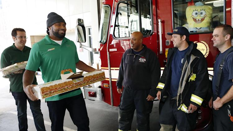 "IMAGE DISTRIBUTED FOR SUBWAY - Jared ""The SUBWAY Guy"", left and New England linebacker Jerod Mayo, right, surprise Boston Fire Department with Giant Sub as part of SUBWAY Customer Appreciation Month on Tuesday, Dec. 11, 2012 in Boston. (Photo by Bizuayehu Tesfaye/Invision for SUBWAY/AP Images)"