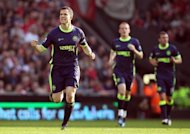 Wigan&#39;s Gary Caldwell (L) celebrates scoring a goal during their Premier League match against Liverpool at Anfield in Liverpool, northwest England, on March 24. Wigan play Chelsea next at Stamford Bridge in London on Saturday