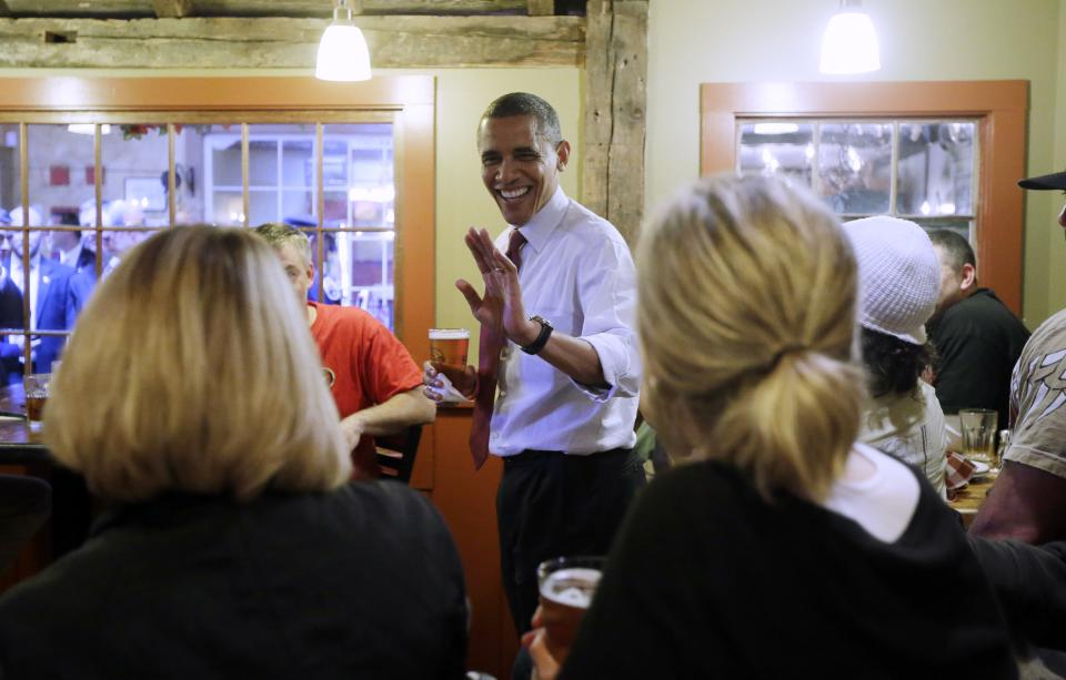President Barack Obama holds his beer as he greets local patrons during an unscheduled visit to the Common Man Restaurant, Saturday, Oct. 27, 2012 in Merrimack, N.H. (AP Photo/Pablo Martinez Monsivais)